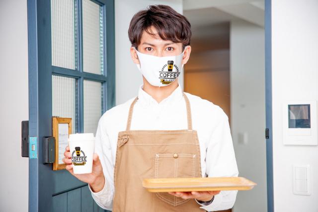 カップに付いているロゴと同じロゴがデザインされたオリジナルマスクをつけたカフェスタッフ